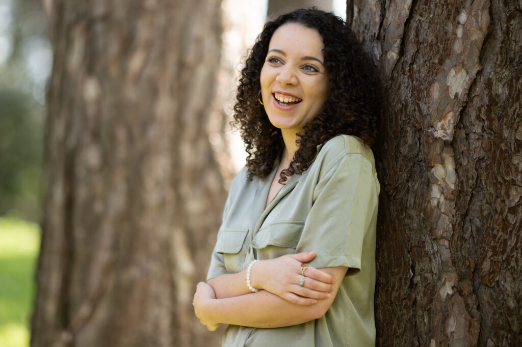 Image of the new poet in residence, leaning against a tree and smiling