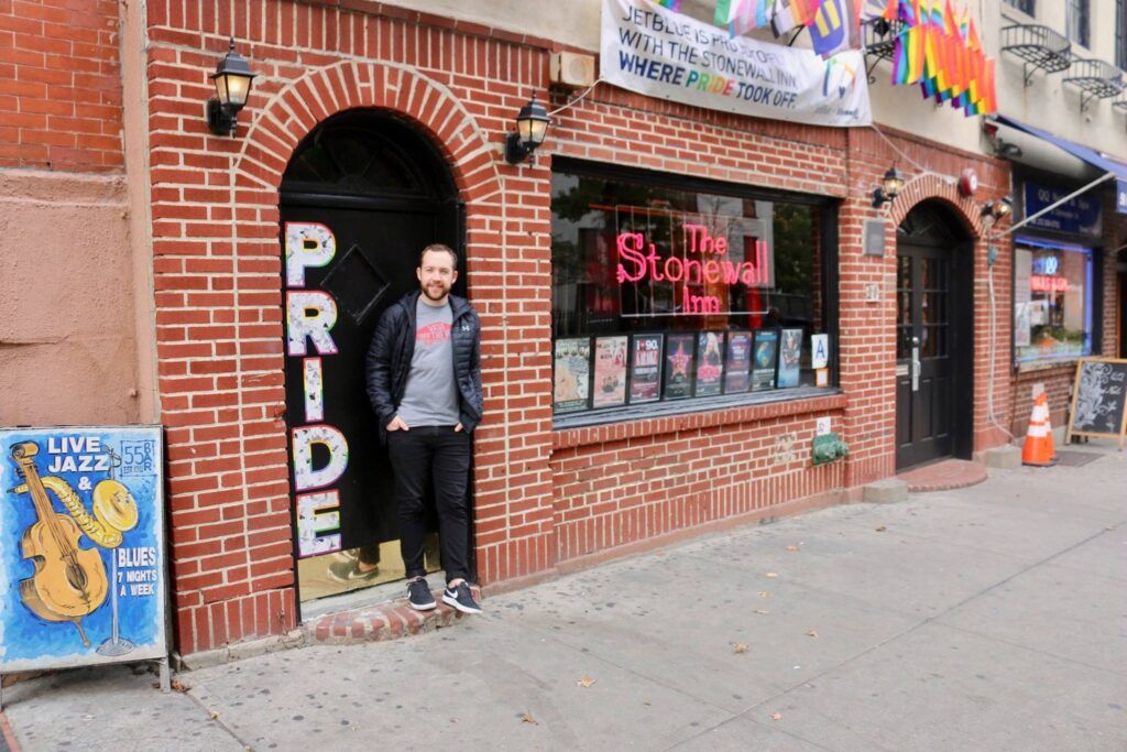 Jacob Ellis our Lead Change Maker smiling and standing in front of the Stonewall Inn which displays a sign saying 'where pride took off'.