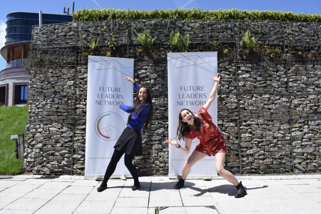 Leah and other woman doing funny poses and standing in front of a sign saying 'Future Leaders Network'